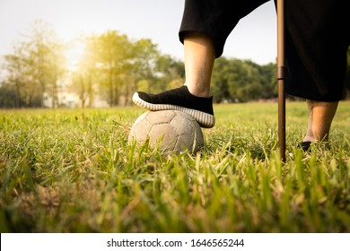 Asian senior woman exercising,excellent healthy with soccer ball, female elderly with walking stick,playing with old football,training leg muscles of old people, health care,good healthy lifestyle