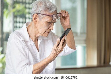 Asian senior woman with eye glasses,try to read messages,gaze at the small text on mobile phone,age related macular degeneration,blurred vision,poor eyesight problems,eye disease of the old elderly