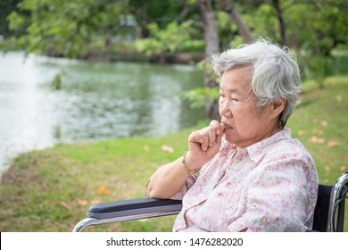 Asian senior woman feeling stressed,worried female bites finger nails in wheelchair outdoor park,elderly with nervous expression,nail biting,anxious with hand on mouth biting her nails,anxiety problem