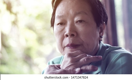 Asian senior woman with hand on face thinking, worry and sad