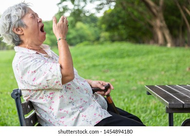 Asian senior woman has sleepy expression,elderly woman yawning covering open mouth with hand,old people feeling yawn,doze,sleepy in outdoor park,being tired after sleepless night,lack of sleep concept