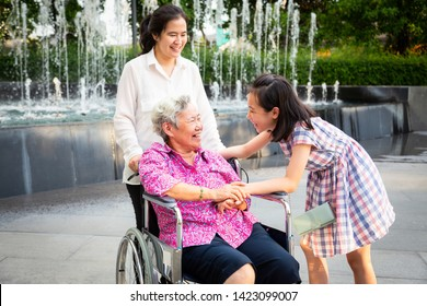 Asian senior woman having happiness and smiling with her daughter and granddaughter on wheelchair at outdoor park,elderly woman is happy with their family,child girl having fun talk,laughing together
