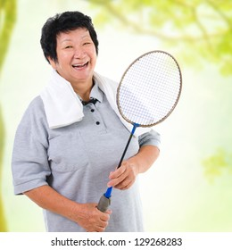 Asian senior woman healthy lifestyle. Happy Asian grandparent holding badminton racket