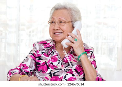 Asian senior woman in her 70s talking on the phone