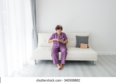 Asian senior woman at home connected on internet