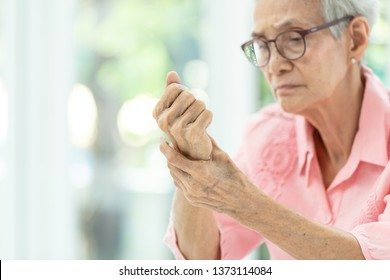Asian senior woman is massaging her wrists,,Elderly woman suffering from pain in hand,arthritis,beriberi