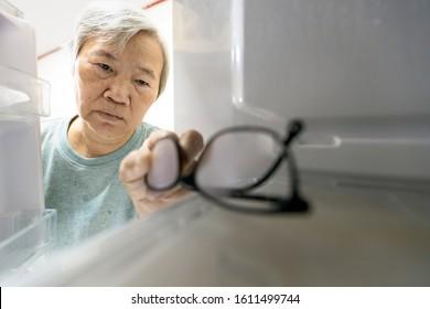 Asian senior woman with memory impairment symptoms,forget her glasses in the refrigerator or storing glasses in the fridge,female elderly having dementia, cognitive impairment, alzheimer's, amnesia