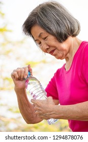 Asian senior woman opening a bottle of drinking water.