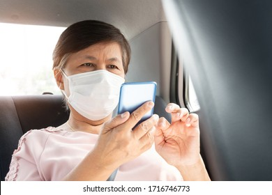Asian senior woman Passenger wear surgical mask for prevent coronavirus or Covid-19 using smartphone while sitting in car. pandemic virus in Public transportation.