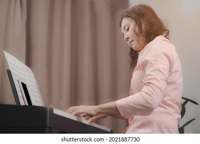 An asian senior woman playing paino with happiness, musician professional in pink shirt looking at paino keyboard with and practicing concentrately.