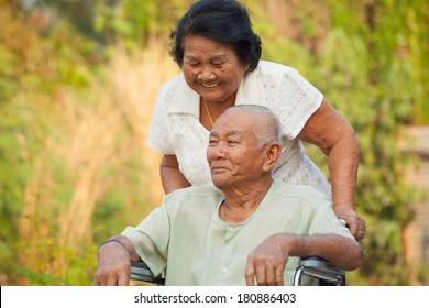 Asian senior woman pushing her disabled husband on wheelchair