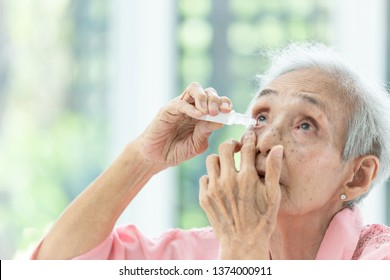 Asian senior woman putting eye drop,closeup view of elderly person using bottle of eyedrops in her eyes,sick old woman suffering from irritated eye,optical symptoms,health concept