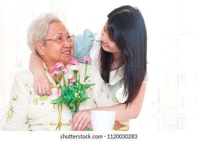 Asian senior woman received carnation flower as mothers day gift from daughter