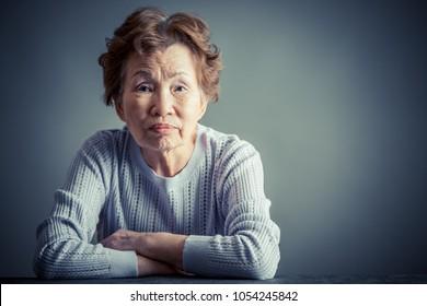 Asian senior woman serious face in studio