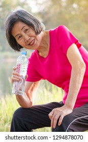 Asian senior woman sitting and smiling with a bottle of drinking water.