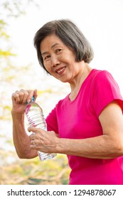 Asian senior woman smiling with a bottle of drinking water.