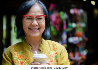 Asian senior woman smiling with  a coffee cup