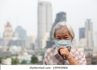 Asian senior woman suffer from cough with face mask protection,elderly woman wearing face mask because of air pollution in the city building;concept of pollution,dust allergies,polluted air,healthcare