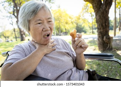 Asian senior woman suffers from choke and cough,clogged up food,elderly people choking during feeding,food might stuck in the throat and suffocate with sever pain injury, asphyxia,suffocation concept