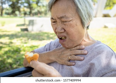 Asian senior woman suffers from choke and cough,clogged up food,elderly people choking during feeding,food might stuck in the throat and suffocate ,health problem, asphyxia,suffocation concept