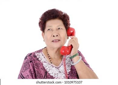 Asian senior woman talking on red vintage phone.