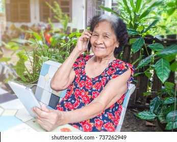 Asian senior woman talking a phone and use digital tablet while sitting in the garden, internet social media, network