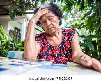 Asian senior woman unhappy while looking at mobile phone and digital tablet abstract loss in profits sitting in the garden, internet social media, network