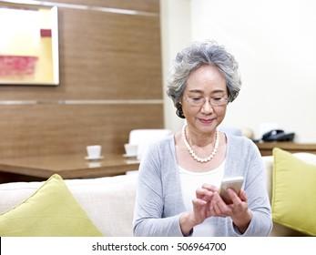 asian senior woman using mobile phone at home