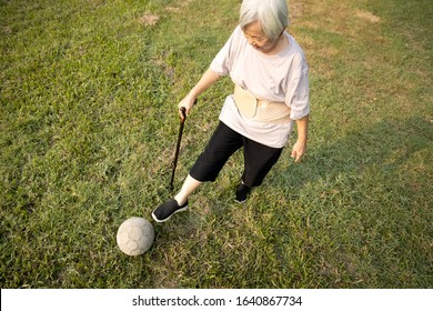Asian senior woman with walking stick,playing with old football,healthy female elderly is kicking soccer ball,physical exercise,training leg muscles,body balance of old people,health care,good healthy
