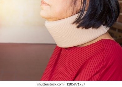 Asian senior woman wearing cervical collar for neck injury.