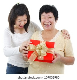 Asian senior women surprises to receiving a present, over white background