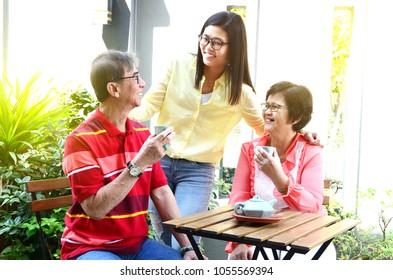 Asian seniors and daughter having tea at garden