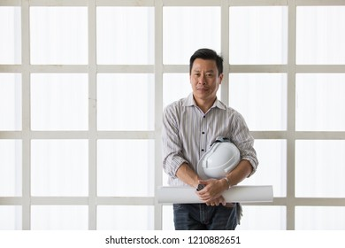 Asian senoir engineer holding white engineering helmet and roll of paper standing in construction site.