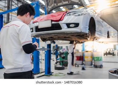 Asian service personnel and Asian car mechanics are writing logs for car damage in an automobile repair center.- car service, repair, maintenance and people concept