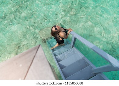 Asian sexy woman in black bikini at overwater villa in luxury resport, vacation holidays concepts background, Tropical Maldives island.