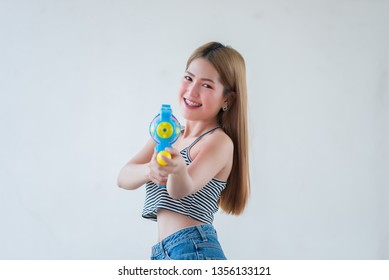 Asian sexy woman with gun water in hand on white background,Festival songkran day at thailand,The best of festival of thai,Land of  smile