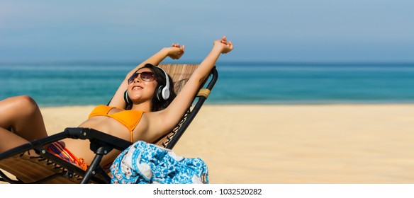 Asian sexy woman  listen to music with headphones are feeling relaxed  on weekends in good weather and sunny day with blur sea background in travel and holiday concept