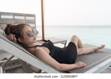 Asian sexy woman sitting on bedchair beach at overwater villa in luxury resport, vacation holidays concepts background, Tropical Maldives island.