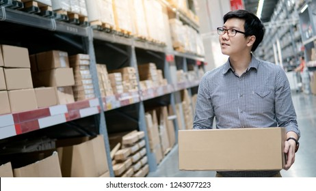 Asian shopper man standing between cardboard box shelves in warehouse choosing what to buy. Shopping lifestyle in department store. Buying or purchasing factory goods. Manufacturing inventory industry