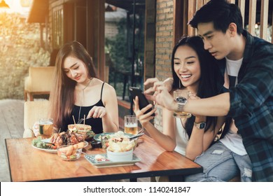 Asian single woman envious with love couple doing take selfie at restaurant.