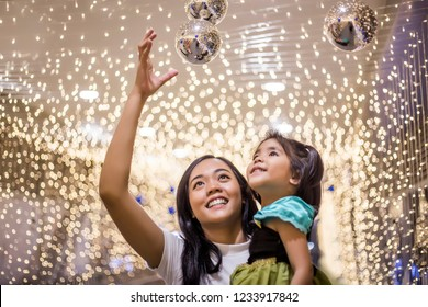 asian sister and kids joy in light decoration at night party. beautiful time to cerebrate concept.