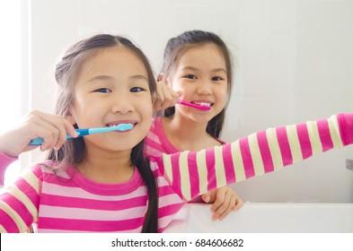 Asian sisters brushing teeth in the bathroom