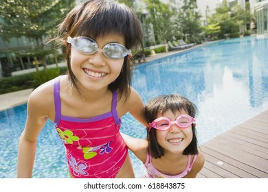 Asian sisters in goggles at swimming pool