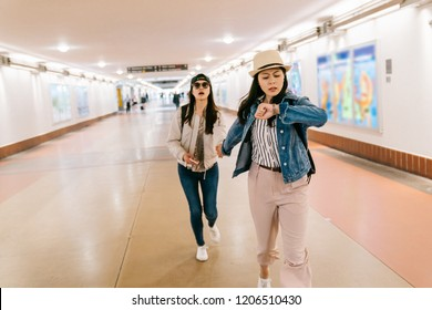 asian sisters are in a rush to catch the train. female travelers running in the passageway in the railway station. backpacker self-guided trip in USA concept.
