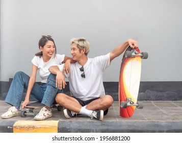 Asian skateboarder couple sitting together on pavement relaxing after exercise. Happy woman sits on a surf skateboard laughing while a man smile. Trendy outdoor recreation sport in Thailand.