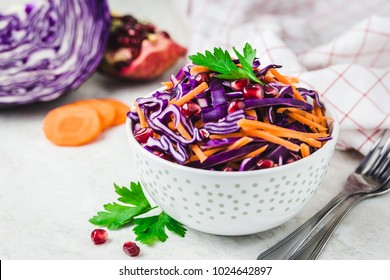 Asian slaw with red cabbage carrot pomegranate salad on white wooden background. Selective focus, space for text.
