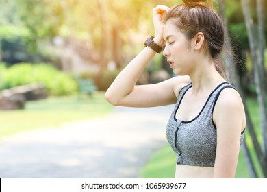a Asian slim woman tired and headache show on her face while exercise in a park