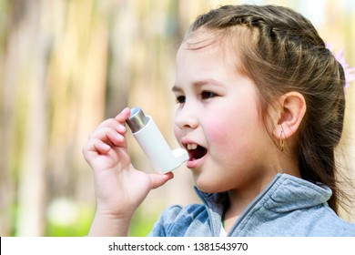 Asian small child using an inhaler during an asthma attack in the park