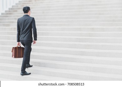 Asian Smart Businessman walking up the stairs.Concept of success business step.