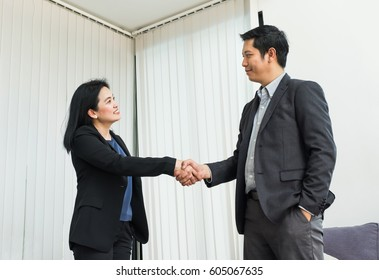 asian Smile Business woman and  business man shaking hand in office,Partnership agreement concept